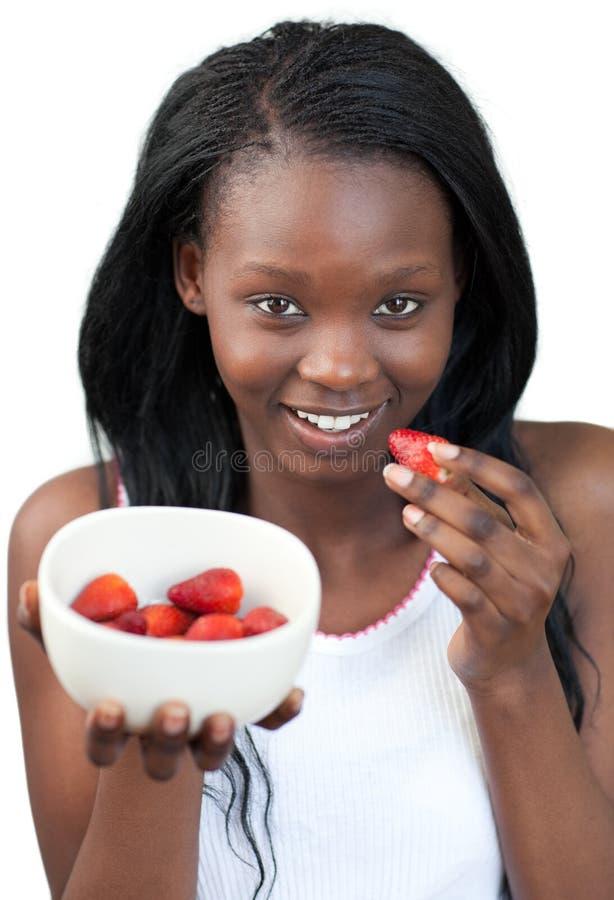 Afroamericano radiante una donna che mangia le fragole immagine stock libera da diritti