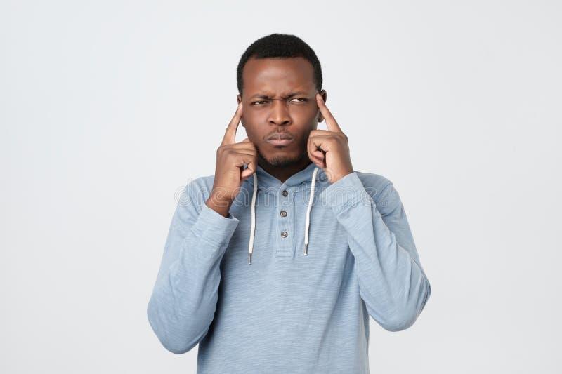 Afroamerikaner, den Mann Finger auf Tempeln hält, wählt beste passende Lösung vor stockfotografie
