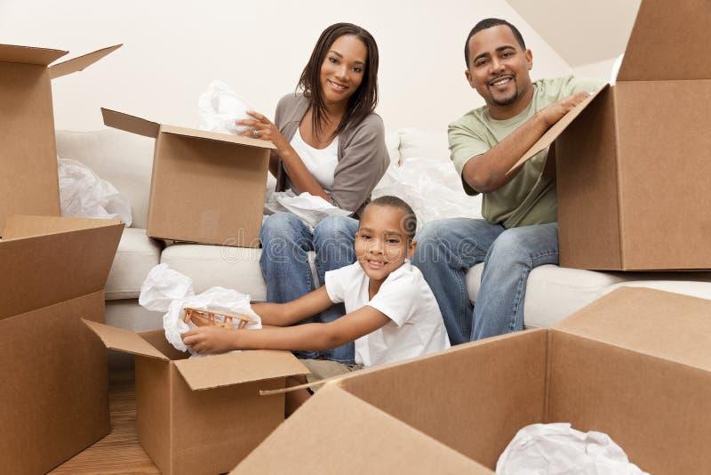 Afroamerikaner-Familie mit den Kästen, die sich nach Hause bewegen stockfotografie