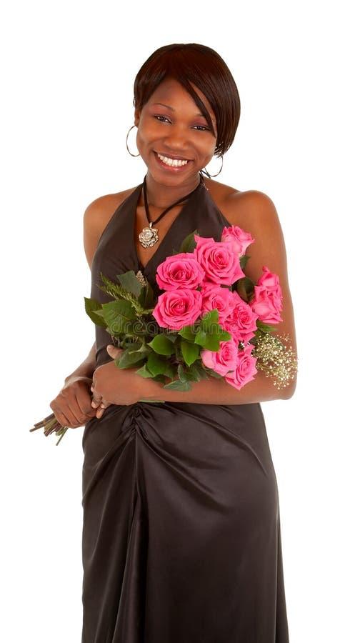 Afroamerikaner-Frau, die mit Rosen aufwirft stockbild