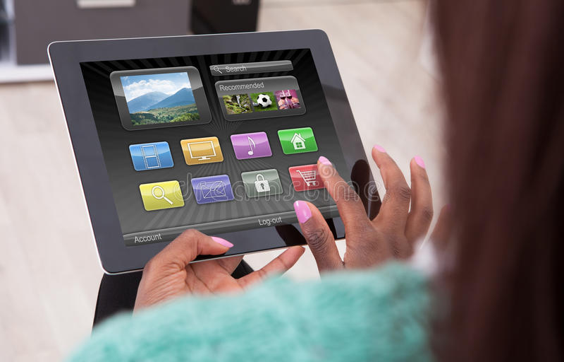 Afroamerikaner-Frau, die zu Hause Digital-Tablet verwendet stockbild