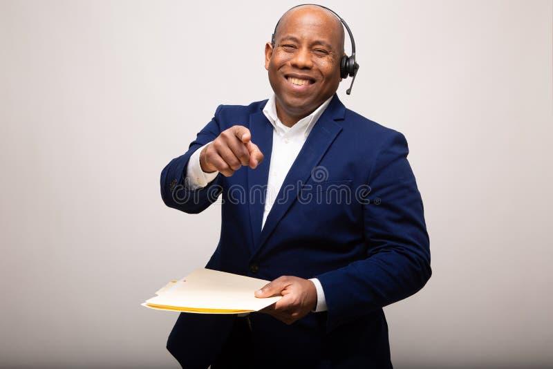 Afroamerikaner-Geschäftsmann-Cheerfully Smiles And-Punkte vorwärts stockfotografie