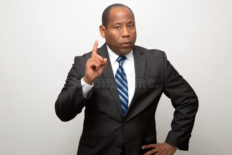 Afroamerikaner-Geschäftsmann, der mit dem Finger im Signal des Rates und des Warnens zeigt lizenzfreies stockbild