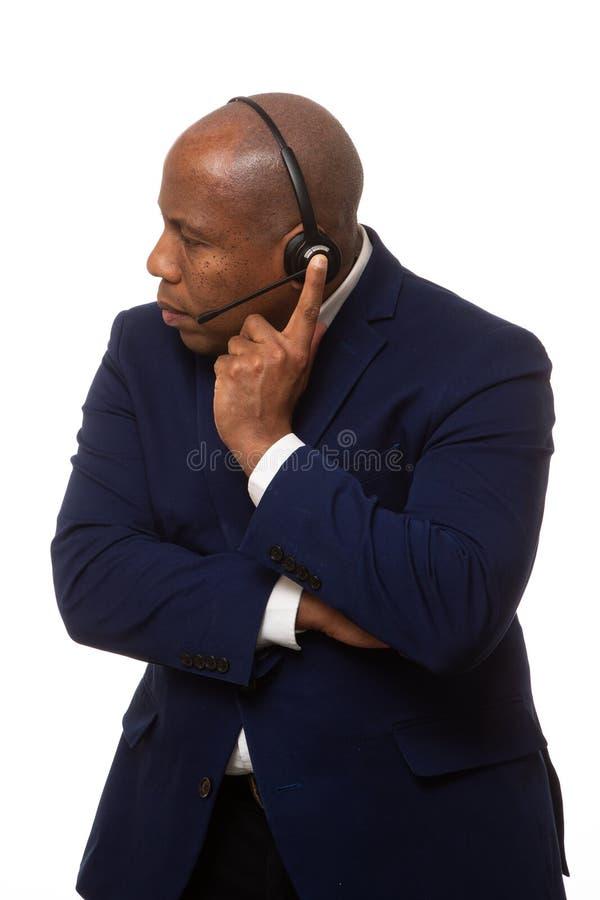 Afroamerikaner-Geschäftsmann Listens Through Headset stockfotos