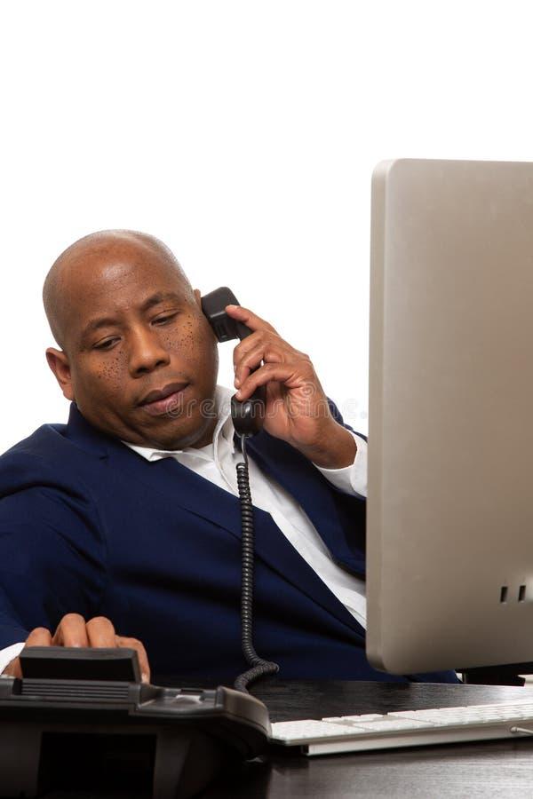 Afroamerikaner-Geschäftsmann Listens On Phone lizenzfreie stockfotos