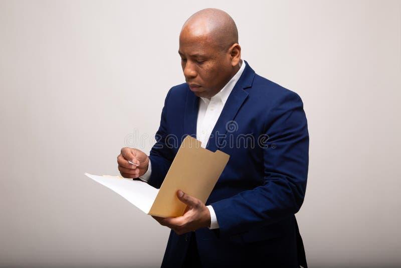 Afroamerikaner-Geschäftsmann Looks Through Folder lizenzfreie stockfotografie