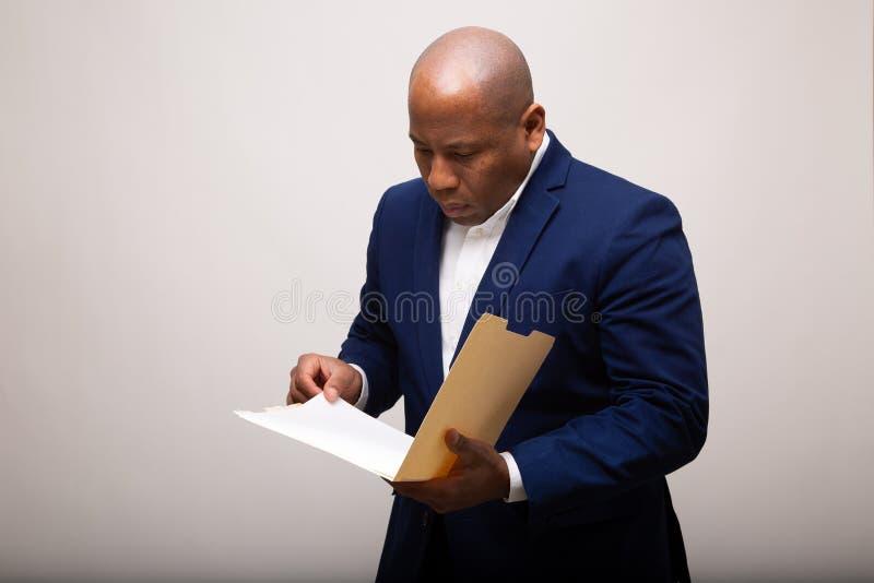 Afroamerikaner-Geschäftsmann Looks Through Folder stockfoto