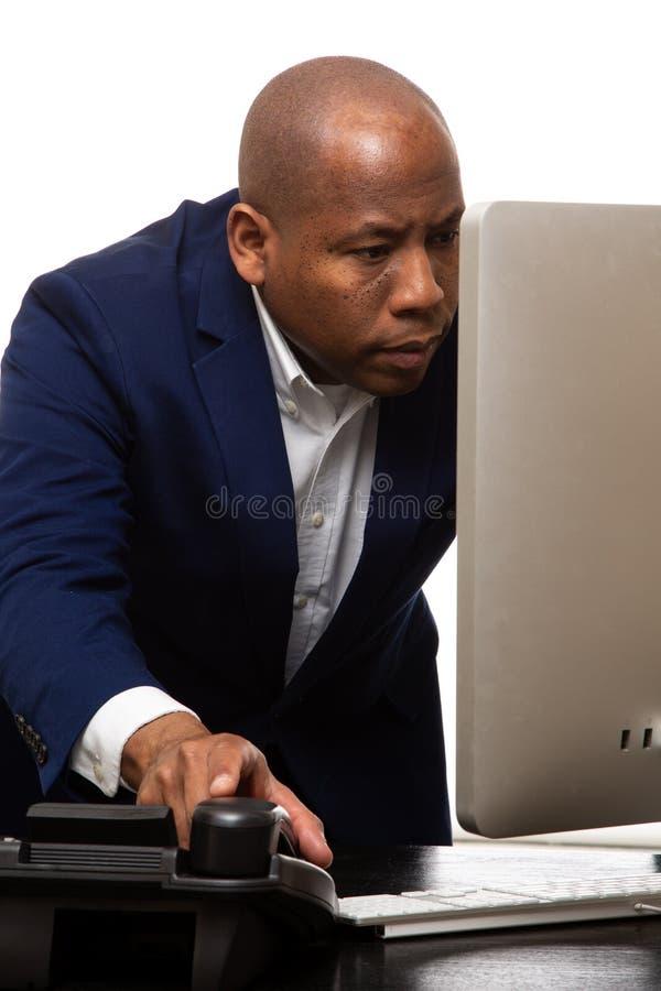 Afroamerikaner-Geschäftsmann Reaching für Schreibtisch-Telefon lizenzfreie stockbilder