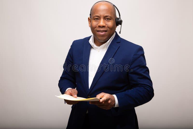 Afroamerikaner-Geschäftsmann-Smiles While Holding-Datei stockbild