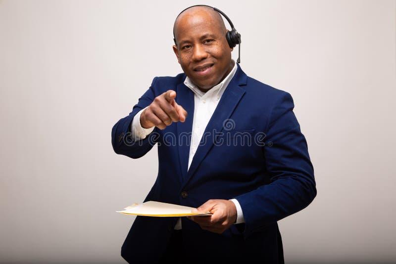 Afroamerikaner-Geschäftsmann Smiles While Pointing und Holding-Datei stockfotografie