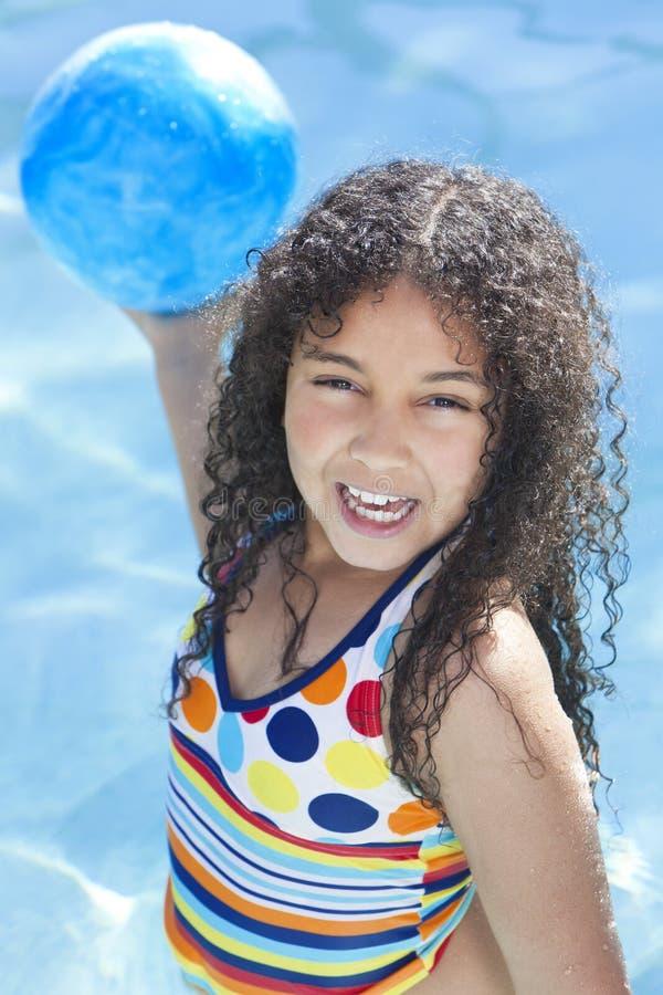 Afroamerikaner-Kind, das im Swimmingpool spielt stockbild