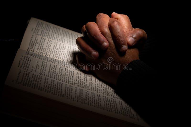 Afroamerikaner-Mann, der mit den Händen auf die Bibel betet lizenzfreie stockfotografie