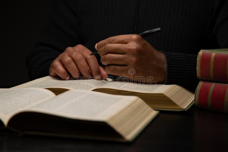 Afroamerikaner-Mann, der am Schreibtisch mit Büchern studiert stockfotografie