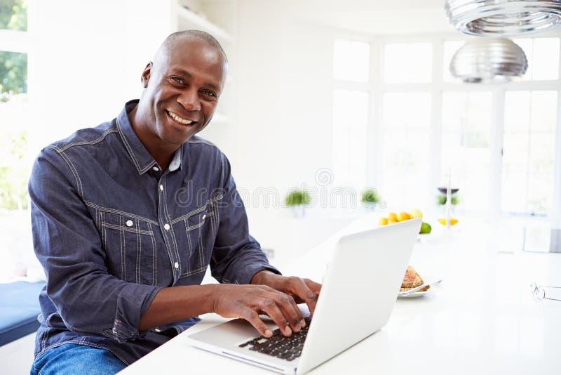 Afroamerikaner-Mann, der zu Hause Laptop verwendet stockbilder