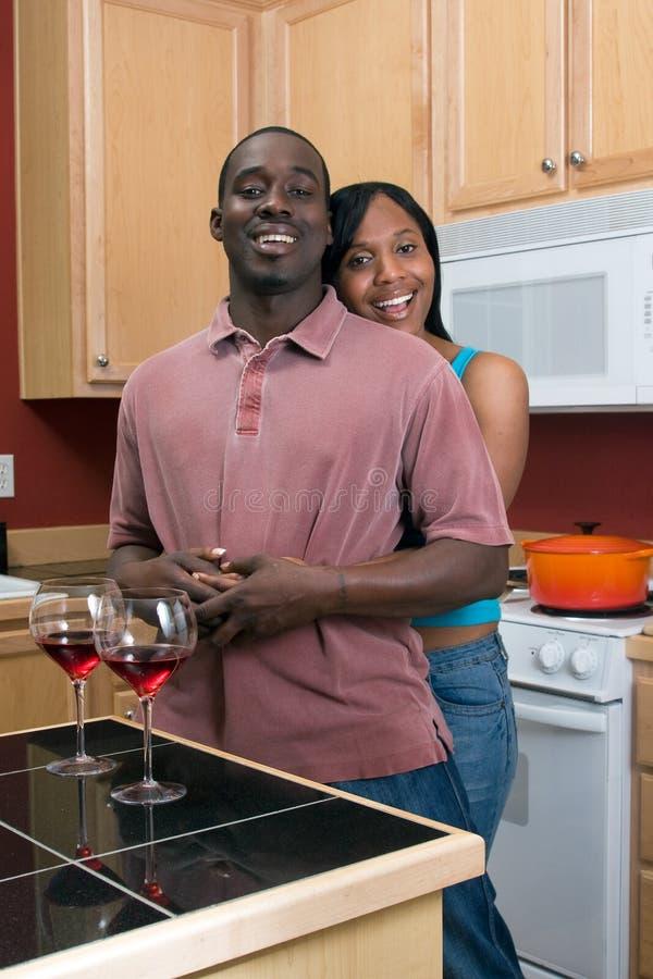Afroamerikaner-Paare, die in der Küche umarmen lizenzfreie stockfotografie
