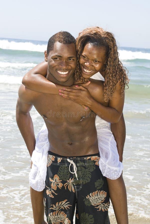 Afroamerikaner-Paare, die am Strand umfassen stockbild