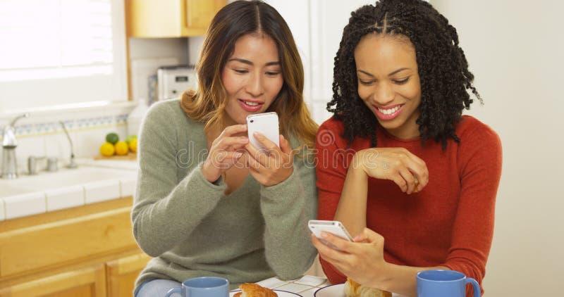 Afroamerikaner- und Asiatsfreunde, die Handys verwenden und Frühstück essen stockbilder