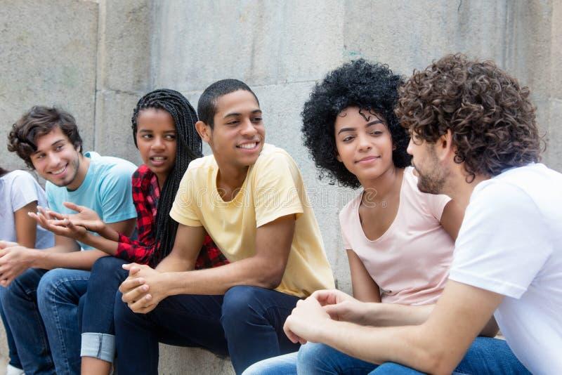 Afroamerikaner- und lateinischejunge Erwachsene, die über Politiken sprechen stockbilder
