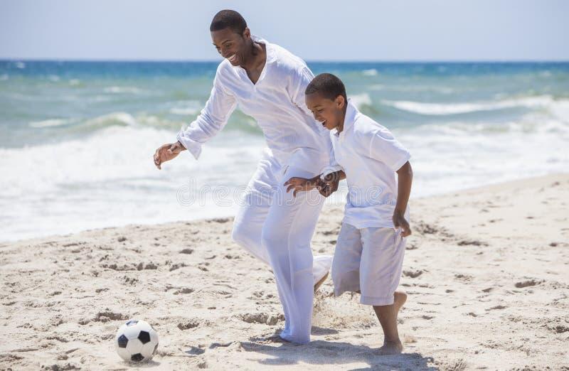 Afroamerikaner-Vater-Son Playing Beach-Fußball-Fußball stockfoto