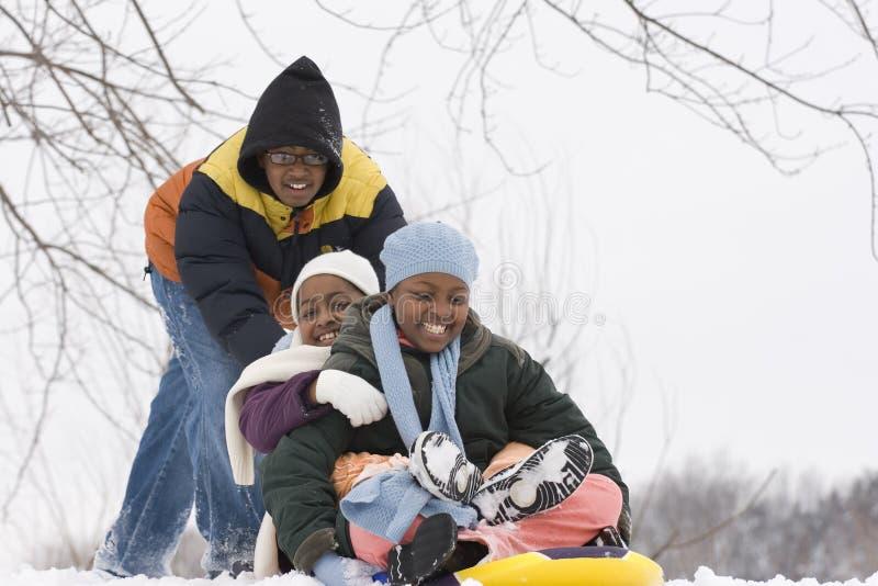 Afroamerikanerbrüder und -schwester, die auf einen Schlitten schieben stockfotos