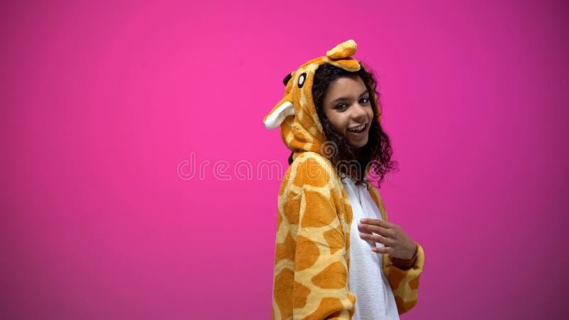 Afroamerikanerdame im lustigen Giraffenkostüm, das auf rosa Hintergrund, Spaß aufwirft stockbilder