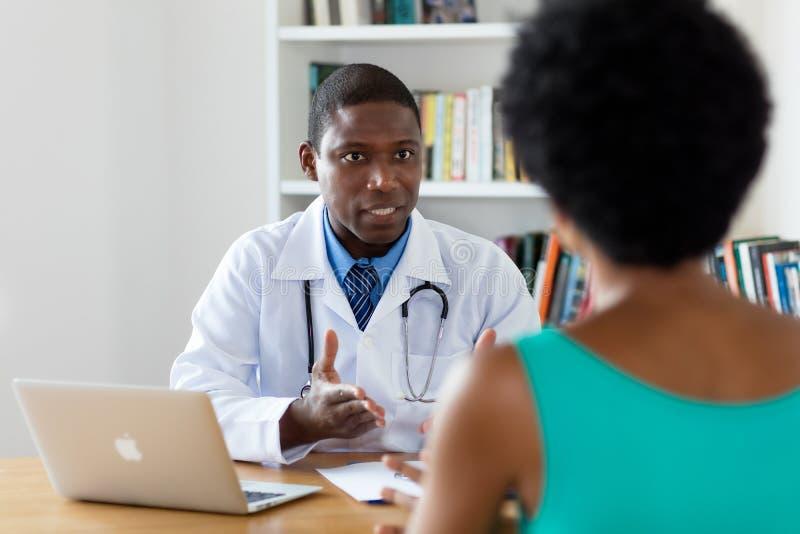 Afroamerikanerdoktor, der über Krebs mit Patienten spricht lizenzfreie stockfotografie