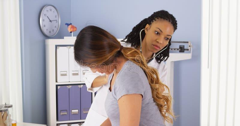 Afroamerikanerdoktor, der auf Herz und Lungen des asiatischen Patienten hört stockfotos