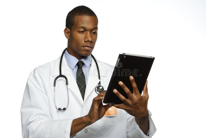 Afroamerikanerdoktor, der die elektronische Tablette, horizontal verwendet stockbilder