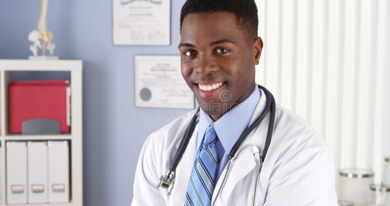 Afroamerikanerdoktor, der im Büro lächelt lizenzfreies stockfoto