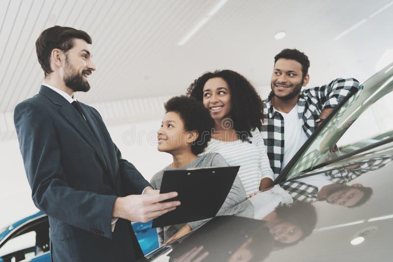 Afroamerikanerfamilie am Auto-Vertragshändler Verkäufer gibt Papiere für Neuwagen lizenzfreies stockbild