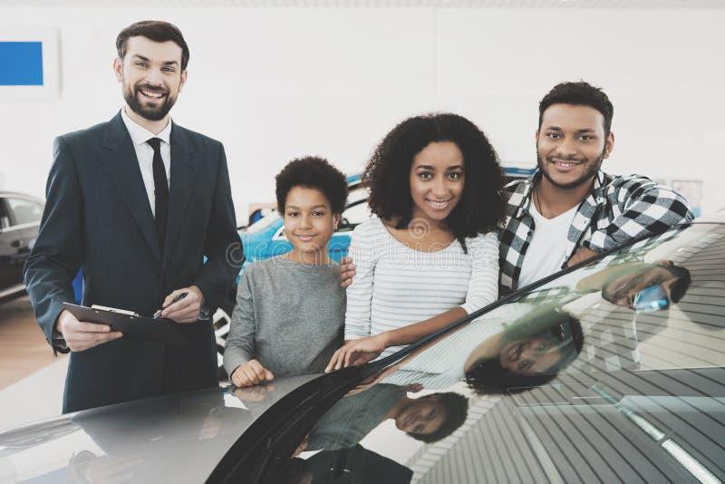 Afroamerikanerfamilie am Auto-Vertragshändler Verkäufer gibt Papiere für Neuwagen lizenzfreies stockfoto