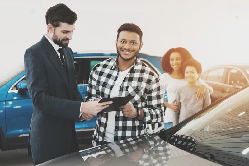 Afroamerikanerfamilie am Auto-Vertragshändler Verkäufer gibt Papiere für Neuwagen stockbilder