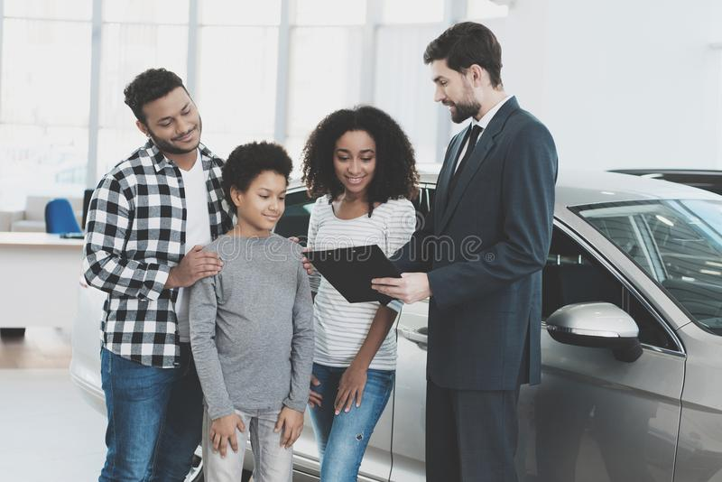 Afroamerikanerfamilie am Auto-Vertragshändler Verkäufer unterzeichnet Papiere für Neuwagen stockbilder