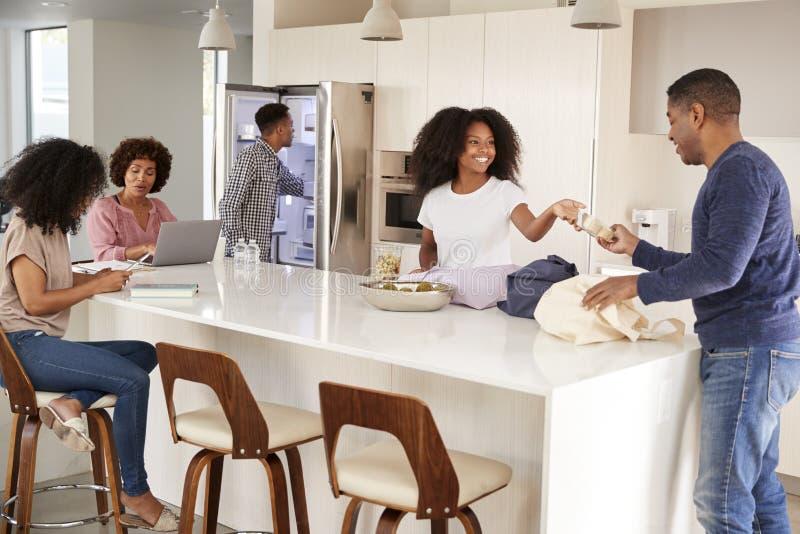 Afroamerikanerfamilie, die Lebensmittelgeschäfte auspackt und zusammen Zeit in ihrer Küche verbringt lizenzfreies stockbild