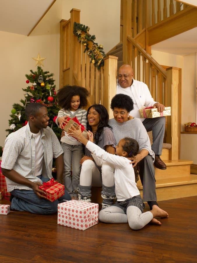 Afroamerikanerfamilie, die Weihnachtsgeschenke austauscht stockfotos