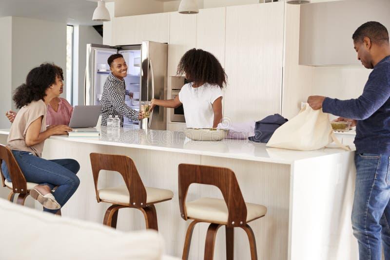 Afroamerikanerfamilie in ihrer Küche, Lebensmittelgeschäfte auspackend und weg setzen sie zusammen stockbilder