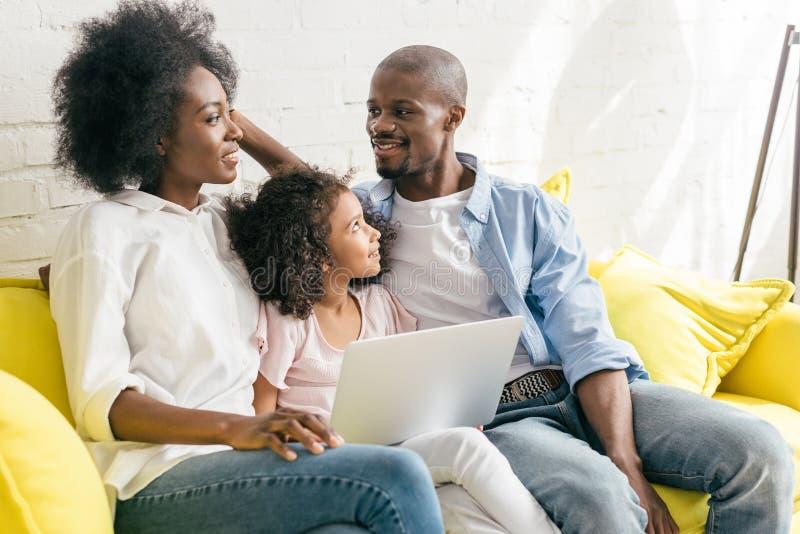 Afroamerikanerfamilie mit dem Laptop, der zusammen auf Sofa stillsteht stockfotografie