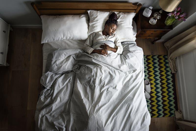 Afroamerikanerfrau auf dem Bettschlafen lizenzfreie stockbilder