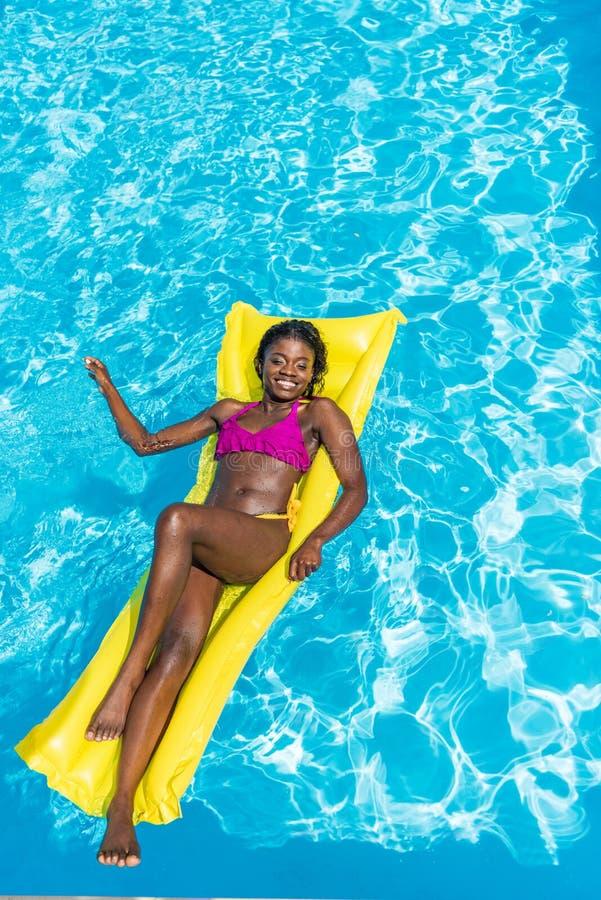 Afroamerikanerfrau, die auf aufblasbare Matratze schwimmt lizenzfreies stockbild