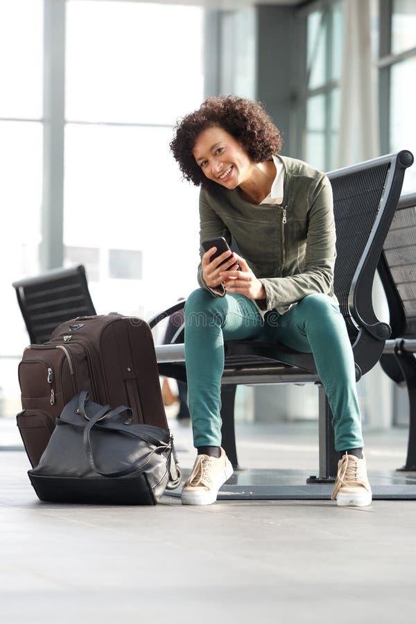 Afroamerikanerfrau, die auf Bank an der Station mit Taschen und Handy sitzt lizenzfreie stockbilder