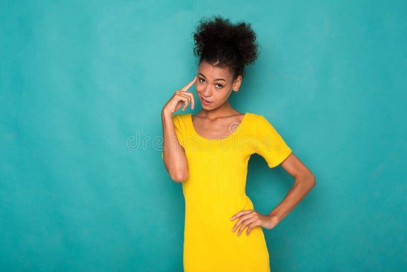 Afroamerikanerfrau, die auf blauem Hintergrund denkt stockfoto