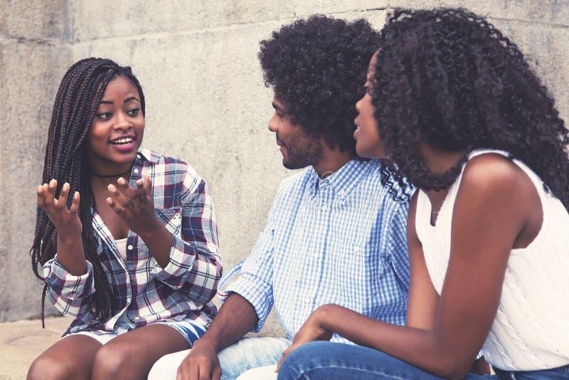 Afroamerikanerfrau, die den Freunden Geschichte erzählt lizenzfreies stockfoto