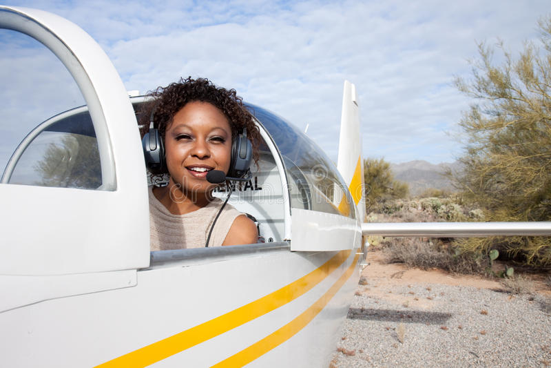 Afroamerikanerfrau, die ein privates Flugzeug fliegt lizenzfreie stockbilder