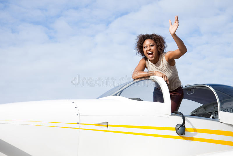 Afroamerikanerfrau, die ein privates Flugzeug fliegt stockbilder