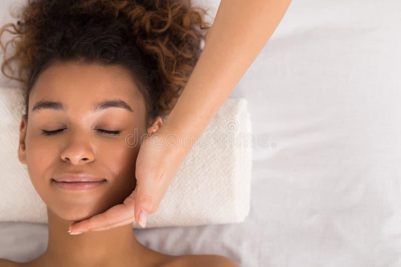 Afroamerikanerfrau, die Gesichtsmassage am Schönheitssalon erhält stockfoto