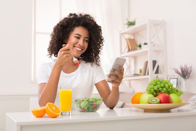Afroamerikanerfrau, die gesunden Salat isst und Smartphone verwendet stockbild