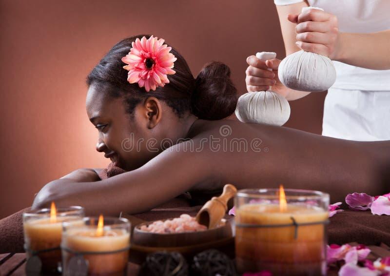 Afroamerikanerfrau, die Kräutermassage am Badekurortsalon genießt stockfoto