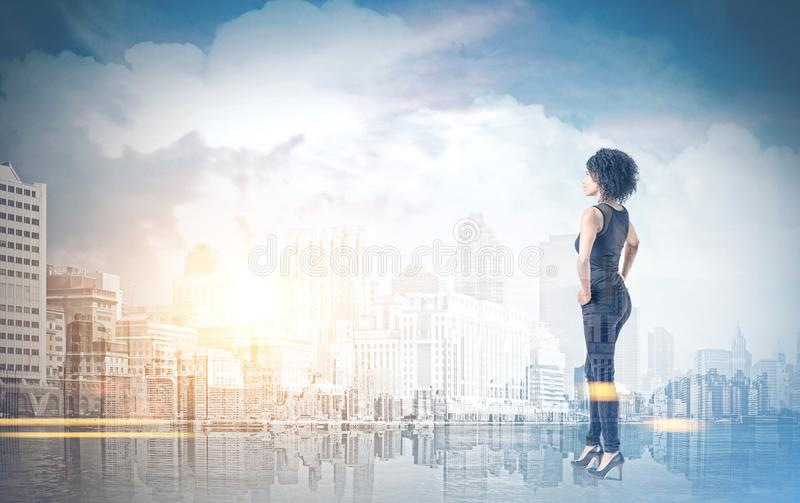 Afroamerikanerfrau mit den Händen auf Taille, Stadt stockbild