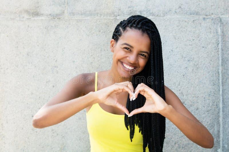 Afroamerikanerfrau mit Dreadlocks in der Liebe, die Herzesprit zeigt stockfotografie