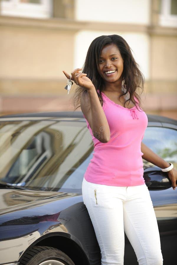 Afroamerikanerfrau mit ihrem neuen Auto lizenzfreie stockfotos